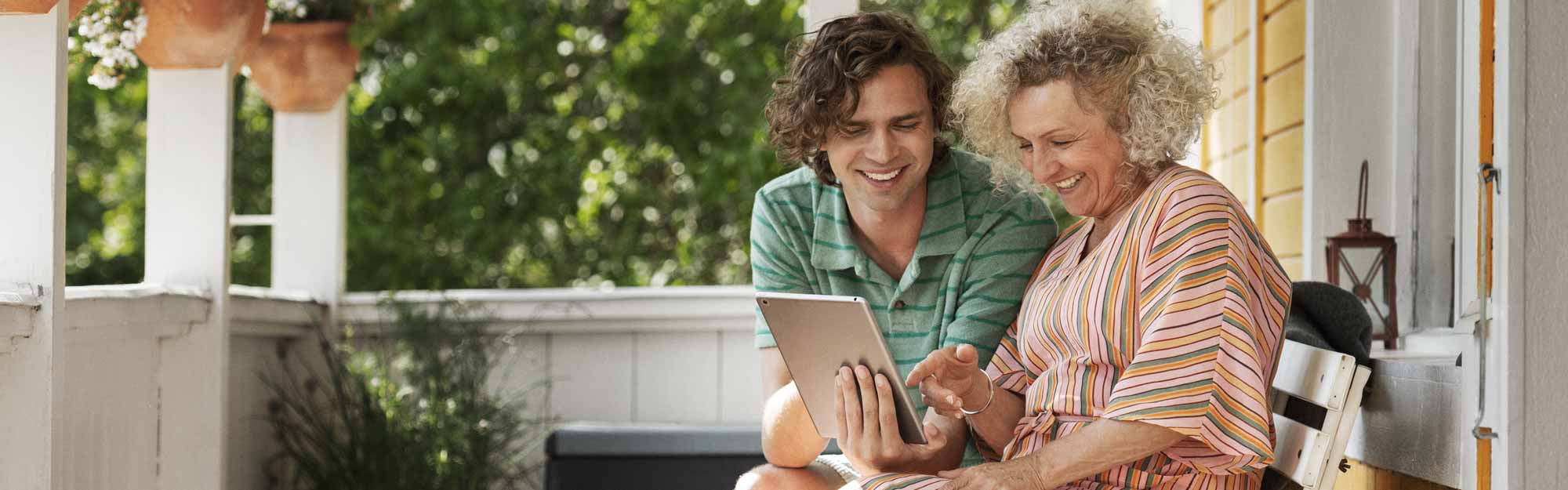 Mother and adult son looking at a laptop on the porch